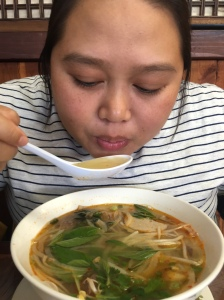 Enjoying her spicy beef noodle soup