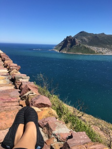 Sitting on a ledge at a scenic stop along Chapmans Peak Drive overlooking Hout Bay.